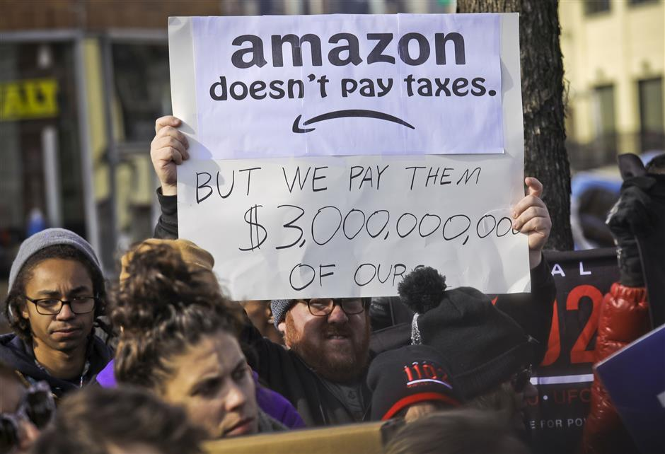 FILE - In this Nov. 14, 2018 file photo, protesters hold up anti-Amazon signs during a coalition rally and press conference of elected officials, community organizations and unions opposing Amazon headquarters getting subsidies to locate in Long Island City, in New York. Local resistance to the online retailer building part of its headquarters in Long Island City was almost immediate. (AP Photo/Bebeto Matthews, File)