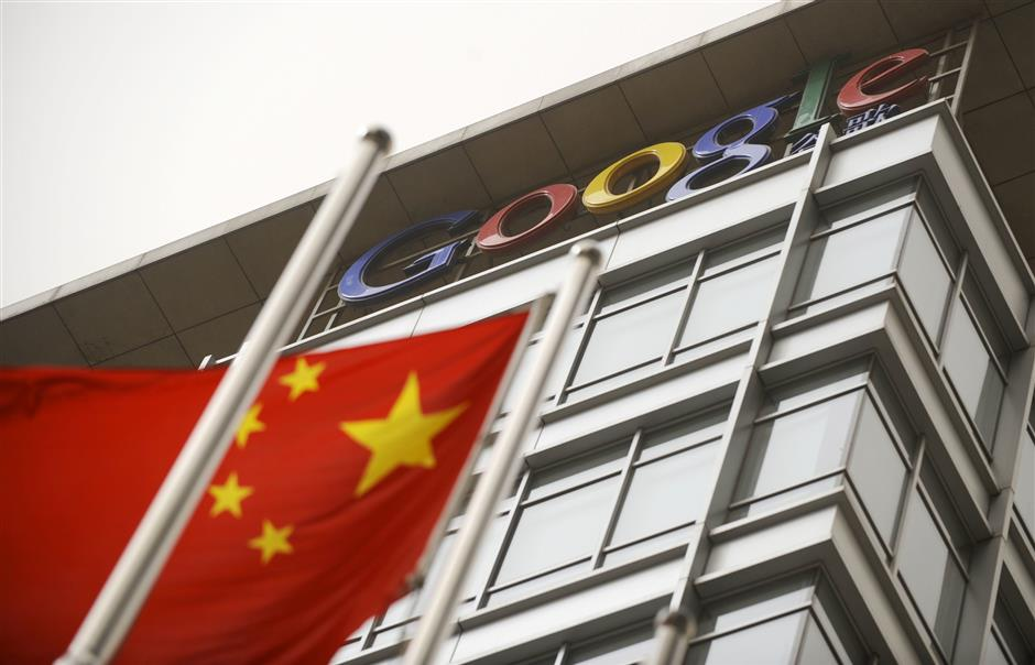 (FILES) This file picture taken on March 22, 2010 shows a Chinese flag flying next to the Google company logo outside the former Google China headquarters in Beijing. After exiting China eight years ago due to censorship and hacking, Google is tuning a mobile search app that would filter blacklisted search results in order to re-enter the market, according to US media reports. / AFP PHOTO / LIU JIN