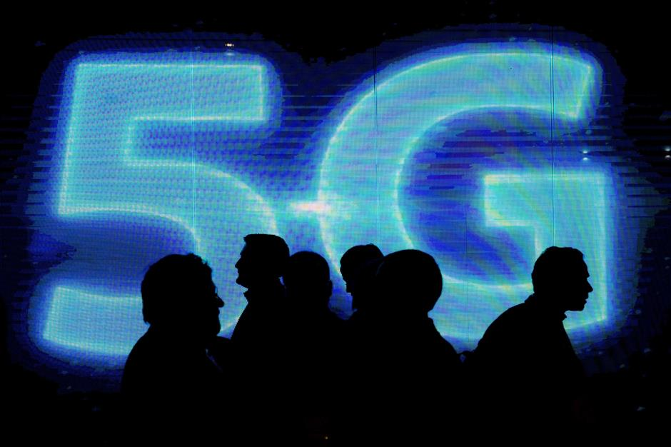 Visitors walk past a 5G logo during the Mobile World Congress on the third day of the MWC in Barcelona, on March 1, 2017. Phone makers will seek to seduce new buyers with artificial intelligence functions and other innovations at the world\'s biggest mobile fair starting today in Spain. / AFP PHOTO / Josep Lago