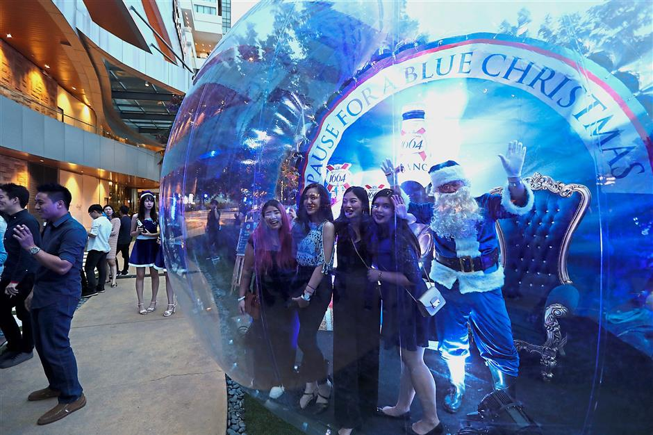 Guests in the giant roving snow globe with a blue Santa during event.