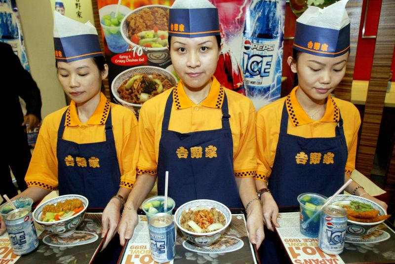 Yoshinoya staff show off three of the restaurant\'s offerings: Green Curry Fish, Kimchi Beef and Spicy and Crispy Chicken.