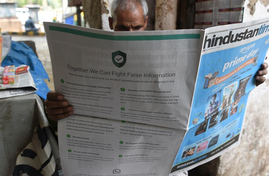 This photo illustration shows an Indian newspaper vendor reading a newspaper with a full back page advertisement from WhatsApp intended to counter fake information, in New Delhi on July 10, 2018.  Facebook owned messaging service WhatsApp on July 10 published full-page advertisements in Indian dailies in a bid to counter fake information that has sparked mob lynching attacks across the country.  / AFP PHOTO / Prakash SINGH