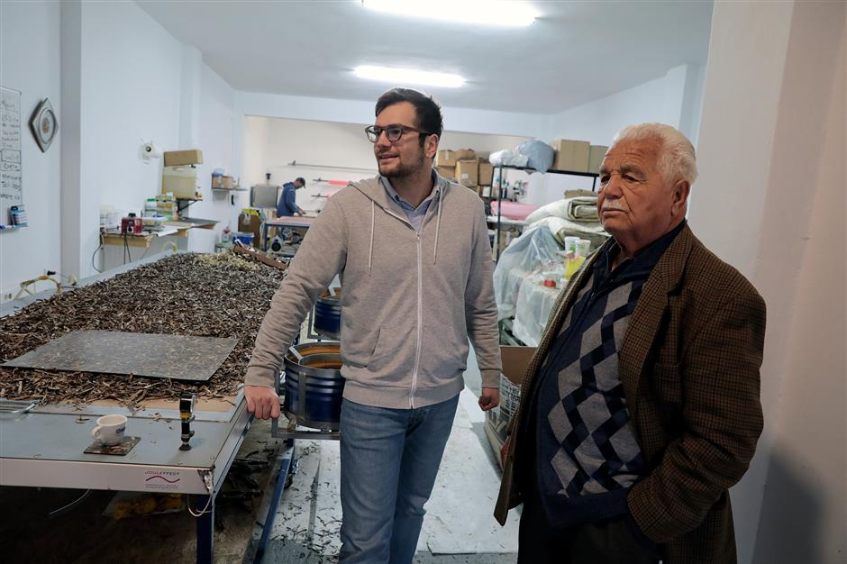 Founder of PHEE Stavros Tsompanidis, 25, and his grandfather Dimitrios Papaderos, 93, are seen at the manufacturing workshop of PHEE in Patras, Greece, March 8, 2018. Picture taken March 8, 2018. REUTERS/Alkis Konstantinidis
