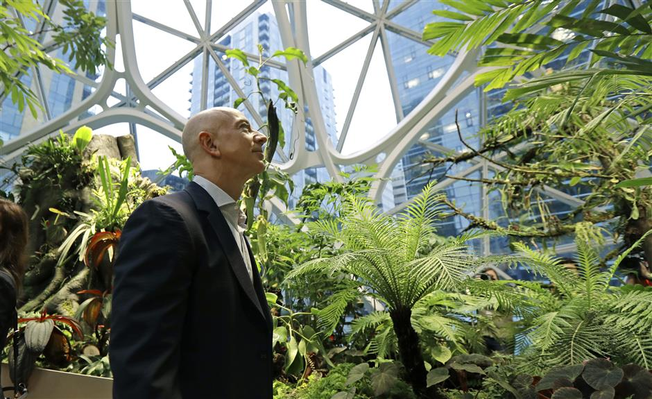 FILE- In this Jan. 29, 2018, file photo Jeff Bezos, the CEO and founder of Amazon.com, takes a walking tour of the Amazon Spheres in Seattle. Amazon has had a complicated few weeks with its cancellation of a New York headquarters Thursday, Feb. 14, 2019, and extortion claims last week related to intimate photos taken by its founder. Experts say the events are unlikely to pose much of a threat to Amazonu2019s business. But the company will continue to face more challenges as it grows larger. (AP Photo/Ted S. Warren, File)