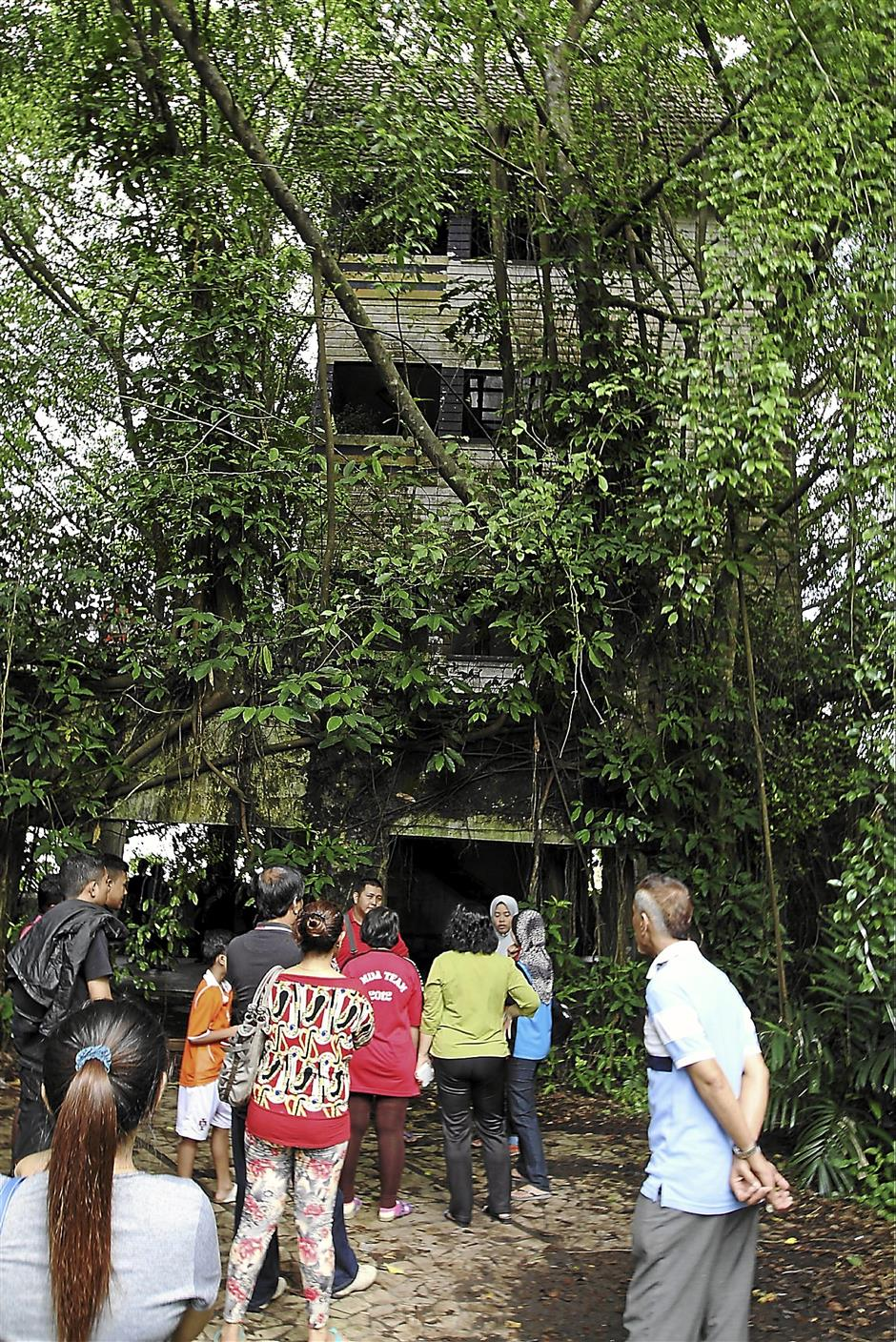 Groups of visitors relating their spooky encounters at Villa Nabila along Jalan Straits View here on Nov 19. The abandoned home became the centre of media attention following the disappearance of a 16-year-old boy who was allegedly last seen entering the area.(LIM CHENG KIAT / THE STAR)