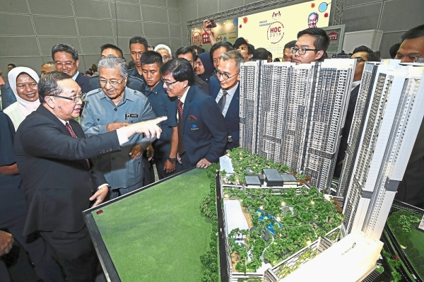 Leong (left) showing Prime Minister Tun Dr Mahathir Mohamad a plan of the groupu2019s M Vertica development in Cheras during the Home Ownership Campaign 2019 Expo.