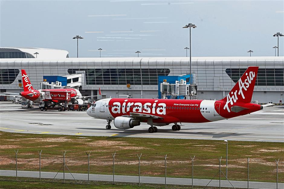 FILE PHOTO: AirAsia planes are seen on the tarmac at Kuala Lumpur International Airport 2 (KLIA2) in Sepang, Malaysia December 13, 2017. Picture taken through glass. REUTERS/Lai Seng Sin/File Photo