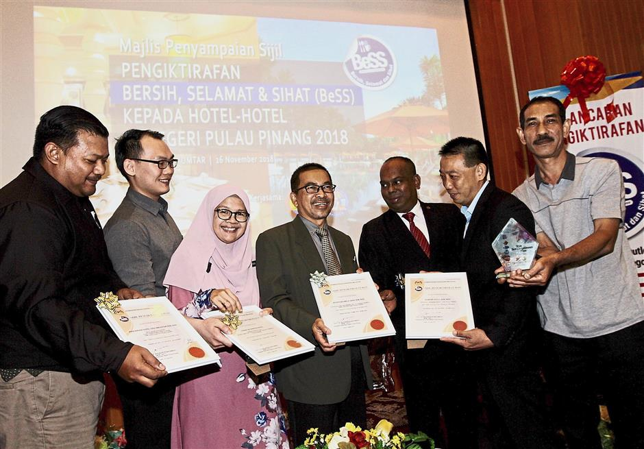 Dr Wan Mansor (centre) and state Health Department deputy director (food security and quality division) Ku Nafishah Ku Ariffin (in tudung) presenting certificates of recognition to (from left) Hotel Seri Malaysia head chief Fazle Abdul Mutalib, Grand Deu2019 Garden Hotel operation and administration executive Dickson Chuah, Royale Chulan Hotel food & beverage manager Roslan Abd Razak, Shangri-Lau2019s Rasa Sayang Resort area hygiene and sanitation manager Khoh Soo Oon and Rainbow Paradise Beach Resort executive chef Mohd Shuhaimi Ahmad.