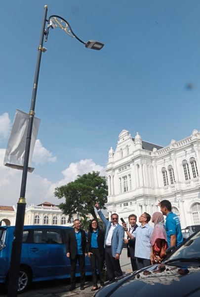 Jagdeep (in blue jacket) pointing to the Terragraph device fixed on a lamp post near the City Hall. Present are (from left) are Wing, Yeoh and council mayor Datuk Yew Tung Seang. — Photos: ZHAFARAN NASIB/The Star