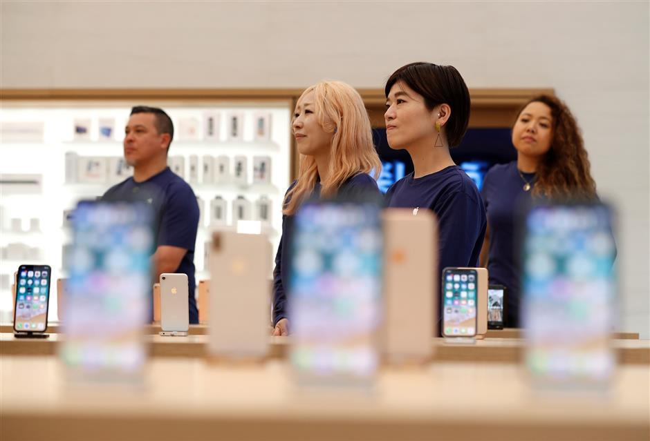 Apple Store staff are seen during a press preview of the Apple Shinjuku store ahead of it\'s grand open in Tokyo, Japan April 5, 2018.  REUTERS/Issei Kato