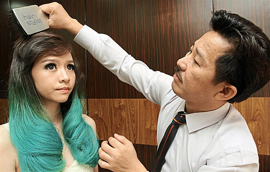 Lim working on the hair of model Michelle Lee Ching Yee.