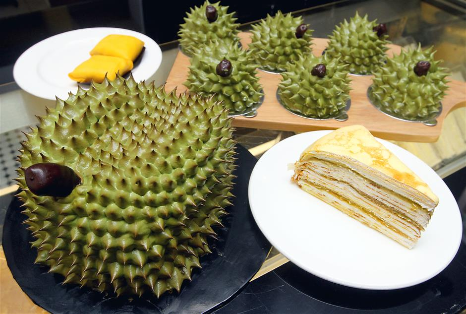 The Mini Durian Imperial is sold for RM16. On the right is the cafe's Durian Mille Crepe.