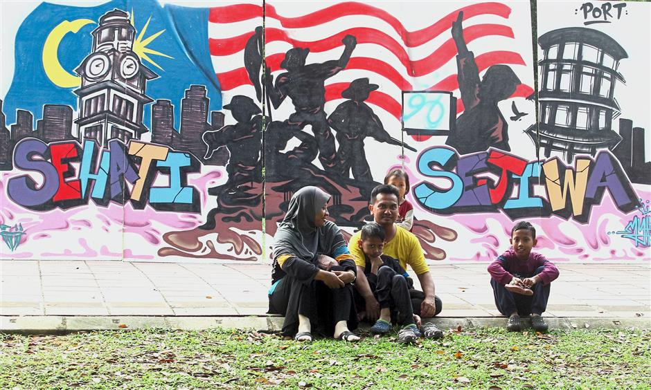 A family enjoying the cool atmosphere of Taiping Lake Gardens near one of the murals at the Pesta Taiping 2017.