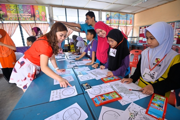 HSBC volunteers conducting the fun activities for pupils and parents to encourage literacy.