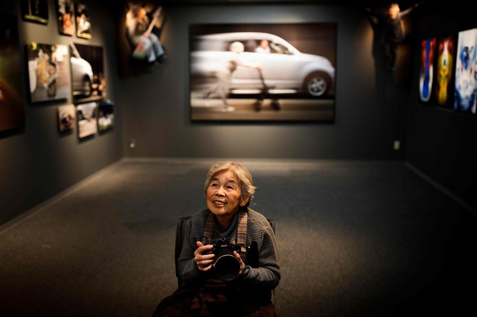 In this picture taken on December 14, 2017, Kimiko Nishimoto poses with a camera in the opening day of her photo exhibition in Tokyo. The madcap Japanese great-grandmother armed with a camera and an appetite for mischief has shot to fame for taking side-splitting selfies -- many of which appear to put her in harm\'s way. / AFP PHOTO / Behrouz MEHRI / TO GO WITH Japan-lifestyle-photography-offbeat-senior-citizens,FEATURE by Alistair HIMMER