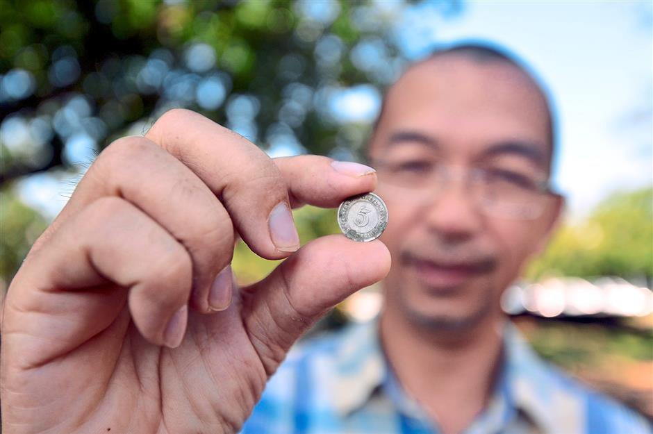 Nearly a hundred: Dr Muhammad Pauzi with one of the 1919 settlement coins found under the houses central pillar.