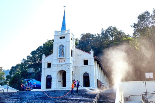 Council workers using jet spray to clean the stairs outside The Shrine.