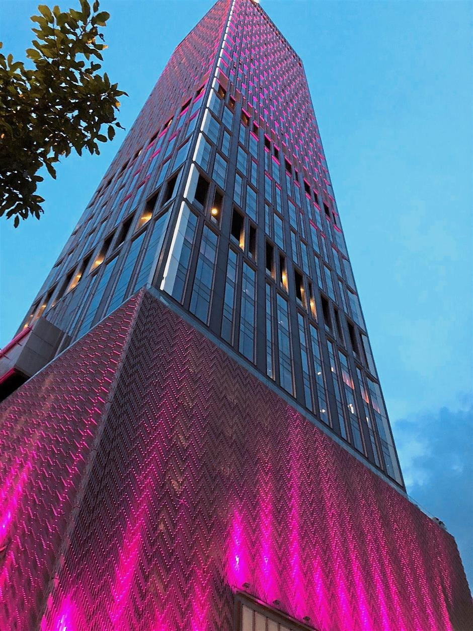 At night, the facade of the W Kuala Lumpur lights up in pink and purple. — WONG LI ZA/The Star