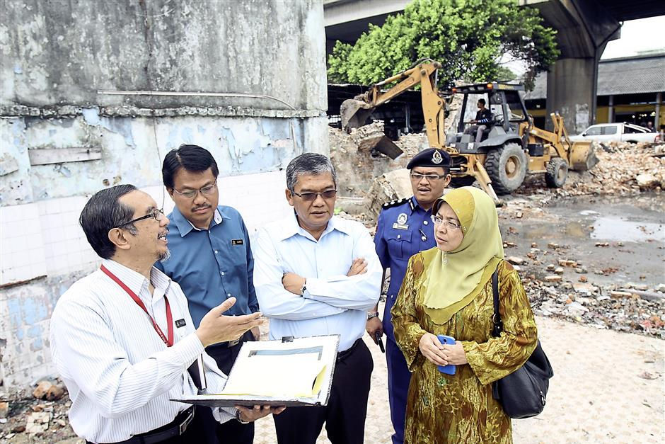 In discussion: Mohammad Yacob (third from left) and Fadzilah Abd Aziz (in tudung) being briefed on the demolition work.