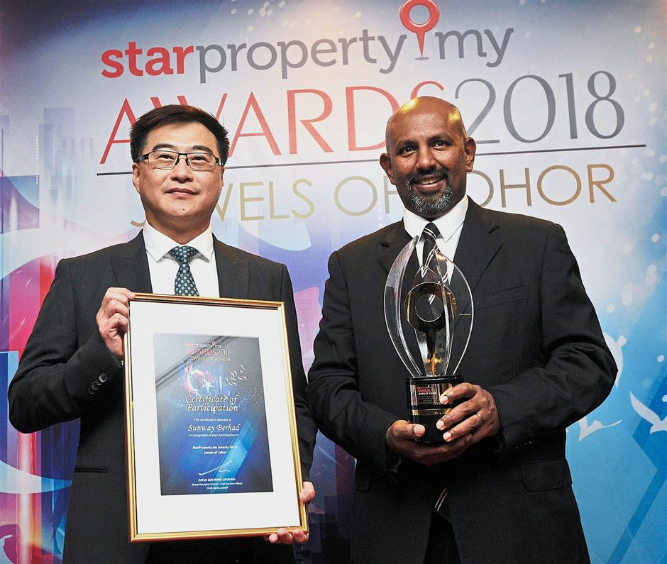 Sunway Berhad deputy managing director Tan Wee Bee (left) and Gerard showing the award the company received during the event.