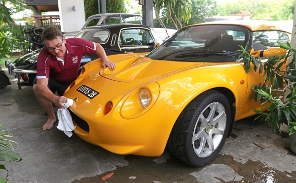 Lacey cleaning one of the cars in his treasured collection, a 2003 Lotus Elise. — Photos: ZHAFARAN NASIB/The Star