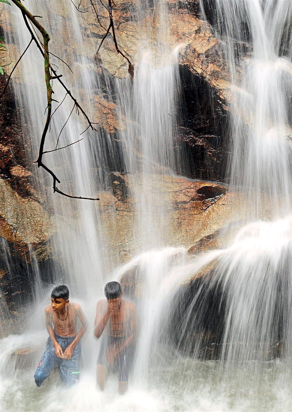Bathing in a waterfall at Taman Rimba Kanching, Rawang. Waterfalls and clear streams have always been an attraction for Malaysians, but with heavy development, we have to double our efforts to protect the environment. - AZHAR MAHFOF/The Star *** Local Caption *** Cool shower: Two boys feeling the full force of the waterfall at Taman Rimba Kanching in Rawang.