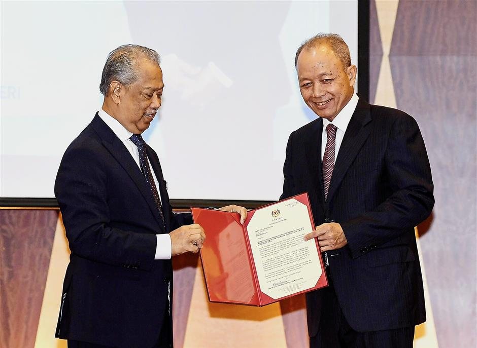 Taking the lead: Home Minister Tan Sri Muhyiddin Yassin (left) presenting the appointment letter to Ariffin. — Bernama