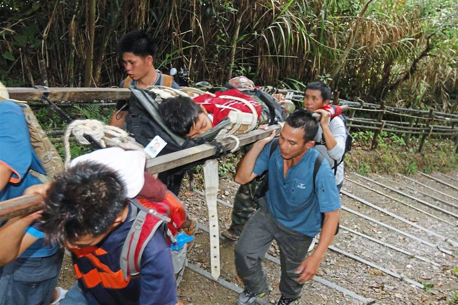 Rescue in progress: Rescuers carrying an  injured climber (inset) arriving at the Timpohon Gate at Kinabalu Park. — NORMIMIE DIUN / The Star