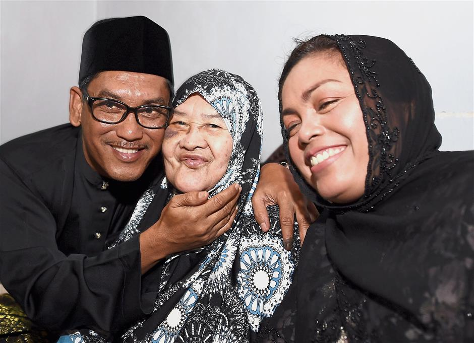 Ahmad Faizal left for his family home in Sungai Rokam to pay his respects to his mother Datin Zaleha Nordin after the ceremony. With them is his wife Dr Nomee Ashikin Mohammed Radzi (right). — Bernama