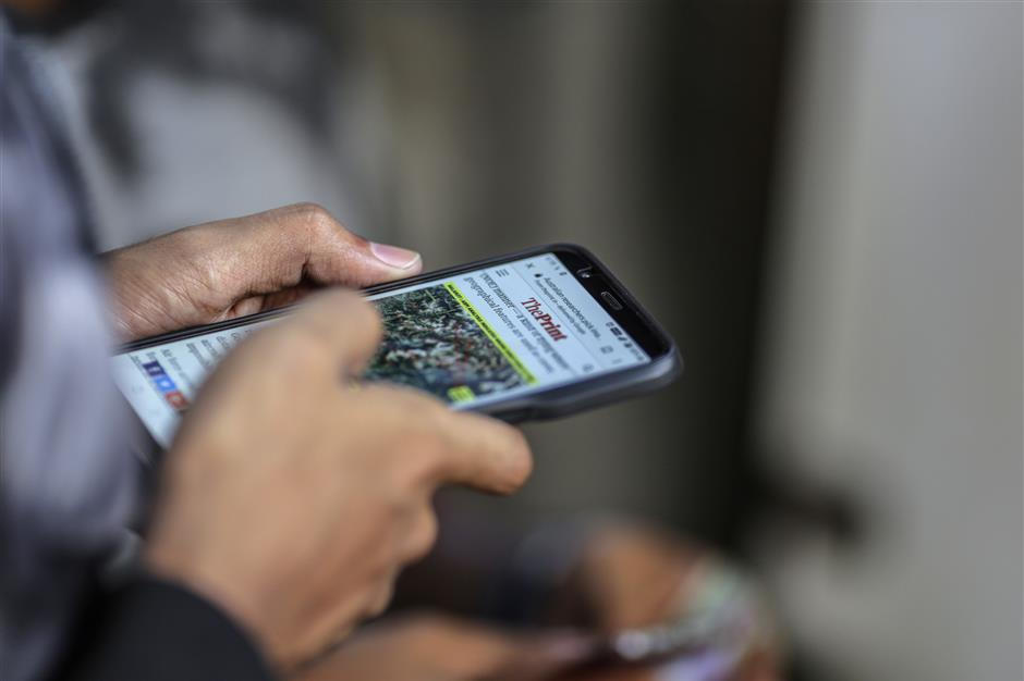 A man reads a news article on a smartphone in Mumbai, India, on Friday, March 28, 2019. Based on the early tallies, as many as 60 percent of Indiau2019s 900 million eligible voters are expected to cast ballots between now and May 19, as the center-left Congress Party tries to seize power from the right-wing Bharatiya Janata Party. As inu00a0otheru00a0electionsu00a0around the world, paid hacks and party zealots are churning out propaganda on Facebook Inc. and the company\'s WhatsApp messenger, along with Twitter, YouTube, TikTok, and other ubiquitous communication channels. Photographer: Dhiraj Singh/Bloomberg