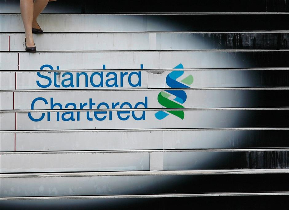 FILE PHOTO: A woman walks down the stairs of the Standard Chartered headquarters in Hong Kong. REUTERS/Bobby Yip/File Photo