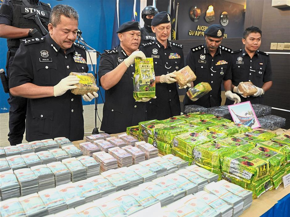 Bukit Aman Criminal Investigation Department director Comm Datuk Seri Mohmad Salleh (second left) showing the confiscated money and drugs during a press conference in George Town, Penang. With him are Penang deputy police chief Deputy Comm Datuk Roslee Chik (left)and Penang Police officers.Star pic by ASRI ABDUL GHANI / The Star / May 04, 2018.