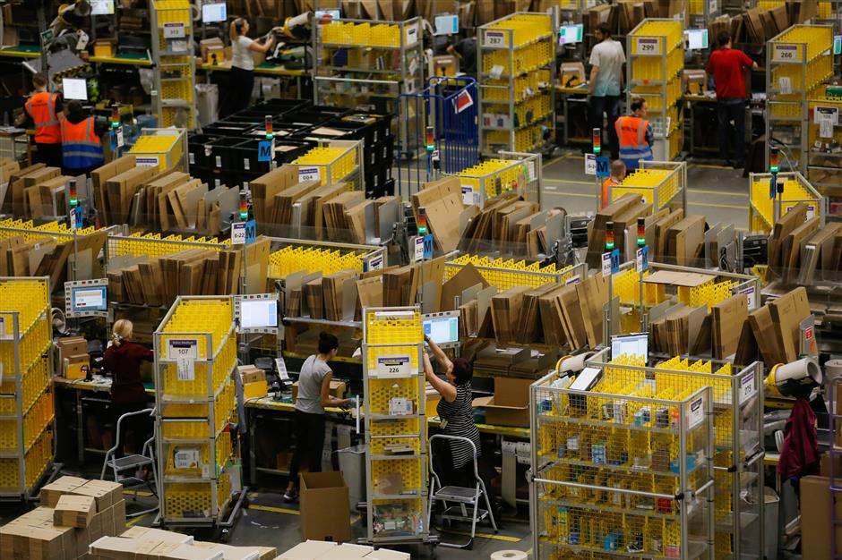 Customers\' orders are processed at an Amazon.com Inc. fulfillment center in Peterborough, U.K., on Wednesday, Nov. 15, 2017. Asu00a0Amazon\'s share of retail sales grows, its corporate stewardship is coming under greater scrutiny. Photographer: Luke MacGregor/Bloomberg