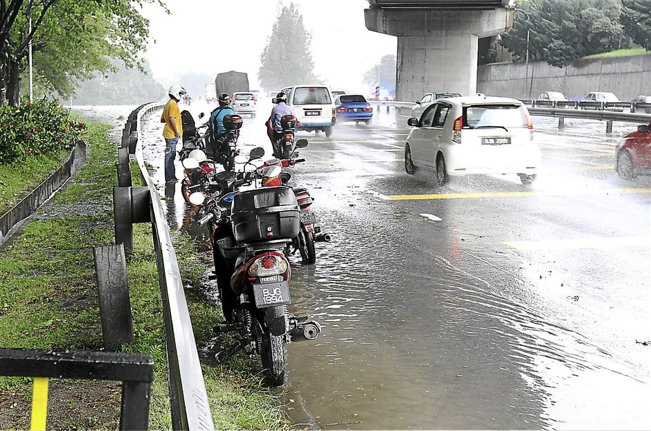 Hazardous: Motorcyclists have to sometimes seek shelter under flyovers, even if it is perilously close to the main road during heavy rains.