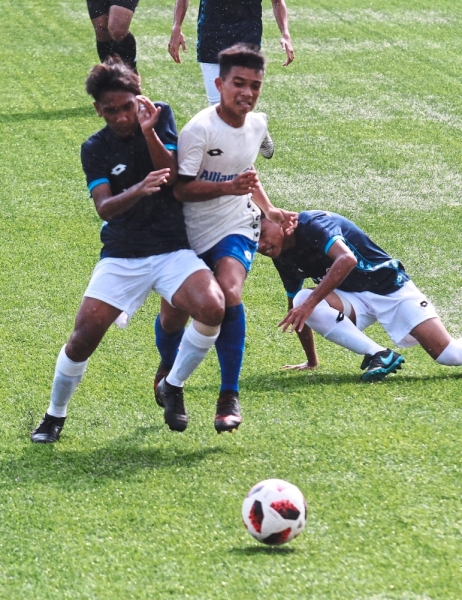 Players from the East Coast region (in blue) trying to get the ball from a Northern region footballer (in white).