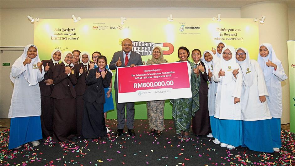 (Centre, from left) Khairul, Education Ministry co-curricular and arts division assistant director Norhayati Mustafa and Tengku Nasariah launching the Petrosains Science Show Competition 2018 at Menara Bank Islam in Kuala Lumpur. With them are students from SMK Puteri Ampang.
