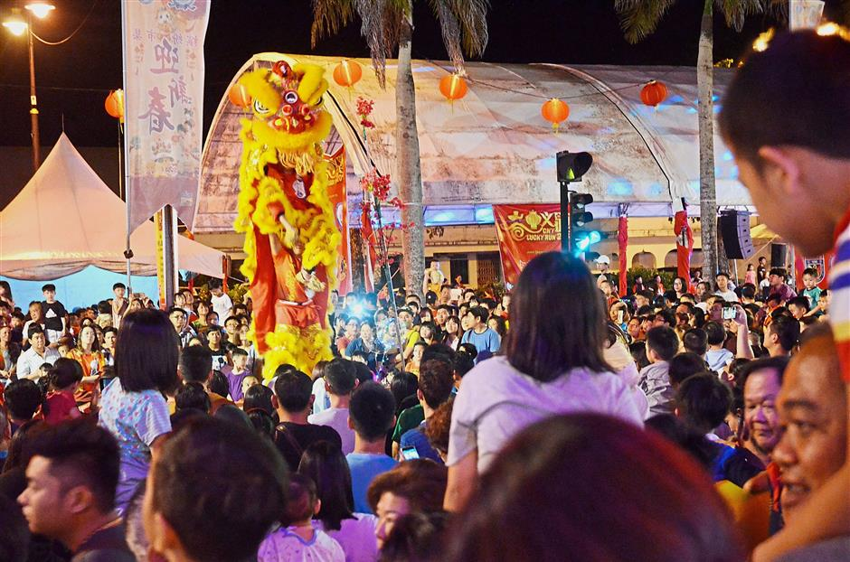 A lion dance performance watched by a large crowd at the bazaar.
