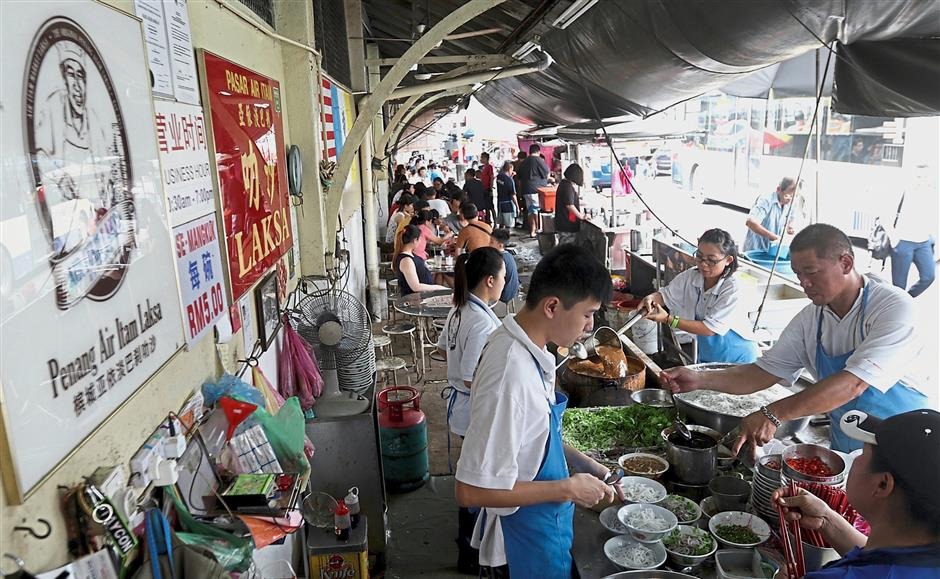 A hawker with his helpers busy preparing ingredients at the Penang Air Itam Laksa stall at the Air Itam market.