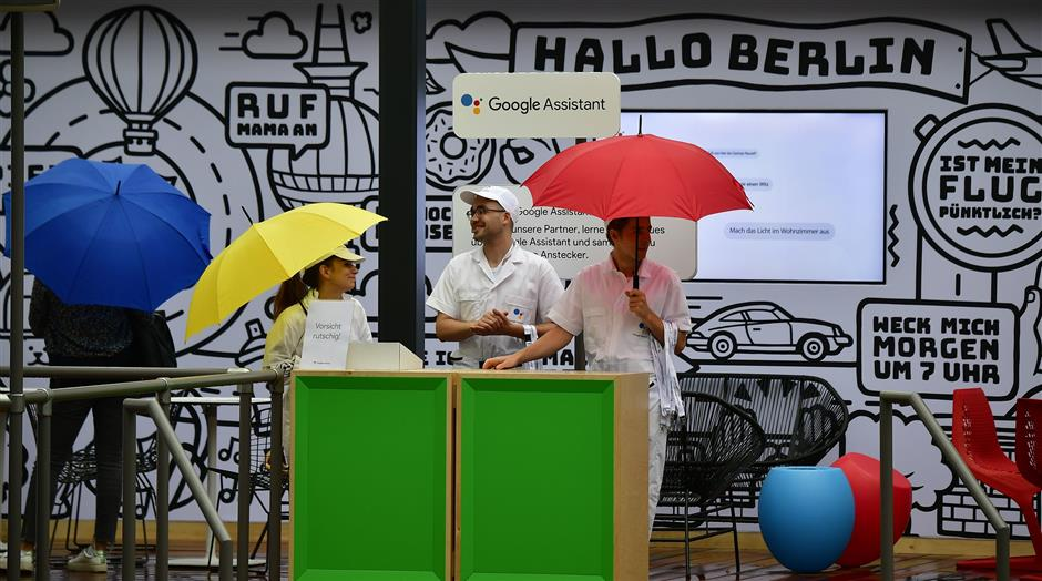 Booth hosts stand at the booth of Google Assistant during a preview day of the IFA, the world\'s leading trade show for consumer electronics and home appliances, in Berlin on August 30, 2018. (Photo by Tobias SCHWARZ / AFP)