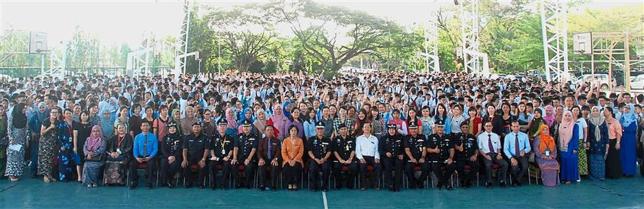 Lim (seated ninth from left) and Fadzillah (on Limu2019s left) with police officers, teachers and students of Kota Kinabalu High School.