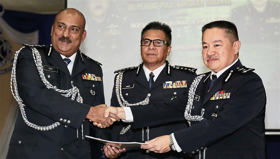 Sarawak police commisioner Datuk Seri Amer Awal (centre) witness the handing over of duty between outgoing state CID chief DCP Datuk Dev Kumar and SAC Denis Leong Soon Kuai. - ZULAZHAR SHEBLEE / THE STAR