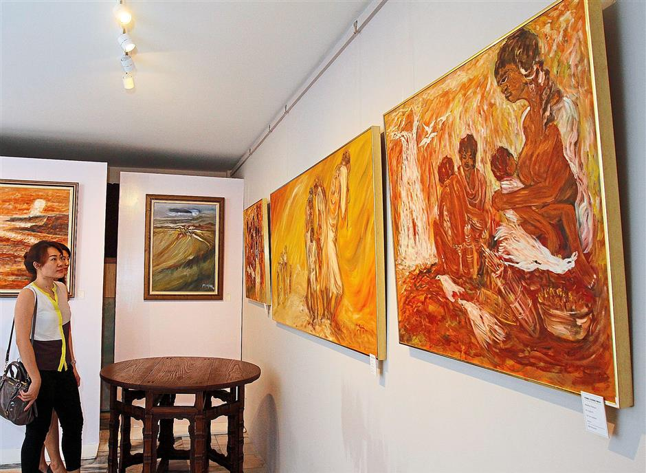 Vibrant works:  Visitors  admiring Yong's  paintings at the exhibition.