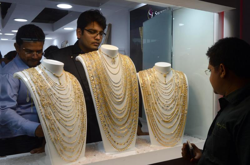 Indian visitors look at gold ornaments displayed in a jewellery shop at the global B2B Jewellery and Gem Fair 2013 in New Delhi on September 21, 2013.The Indian government has this year issued a series of curbs on imports of gold u2013 the second-most expensive item on India\'s import bill u2013 hoping to ease the pressure on the currency - AFP Photo.