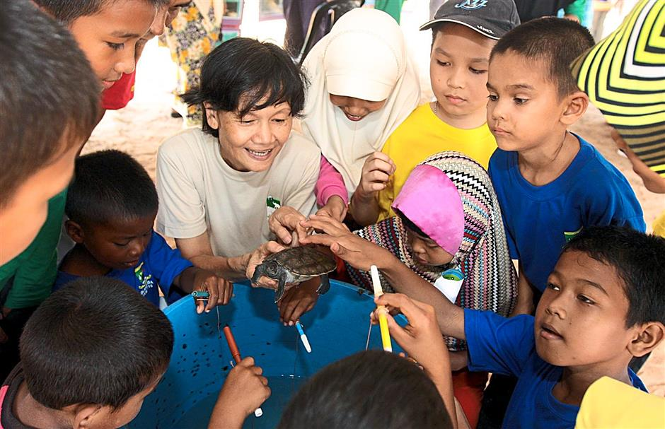 Turtle scientist Dr Chan Eng Heng (centre) allowing schoolchildren to get up close with a river terrapin. - Filepic