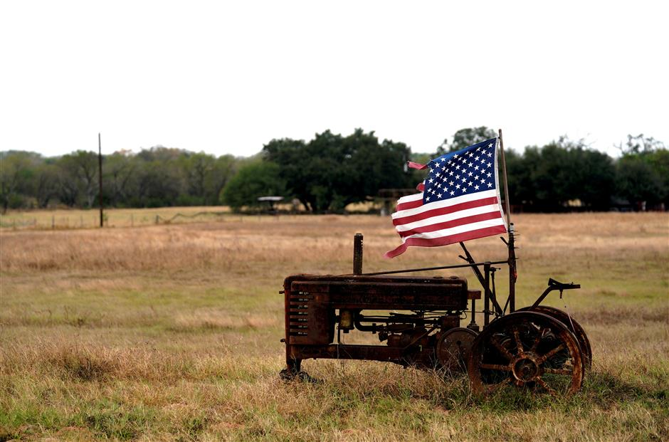 FILE PHOTO: A tattered U.S. flag flies on an old tractor in a farm field outside Sutherland Springs,Texas, U.S. November 8, 2017.  REUTERS/Rick Wilking/File Photo