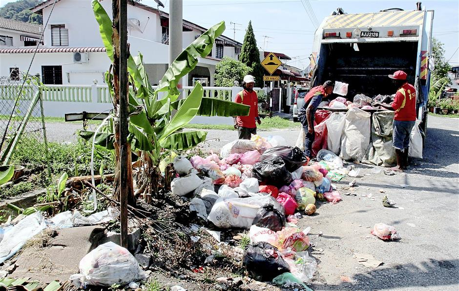 Thankless task: Garbage collectors clearing up an illegal dumpsite in Bercham.