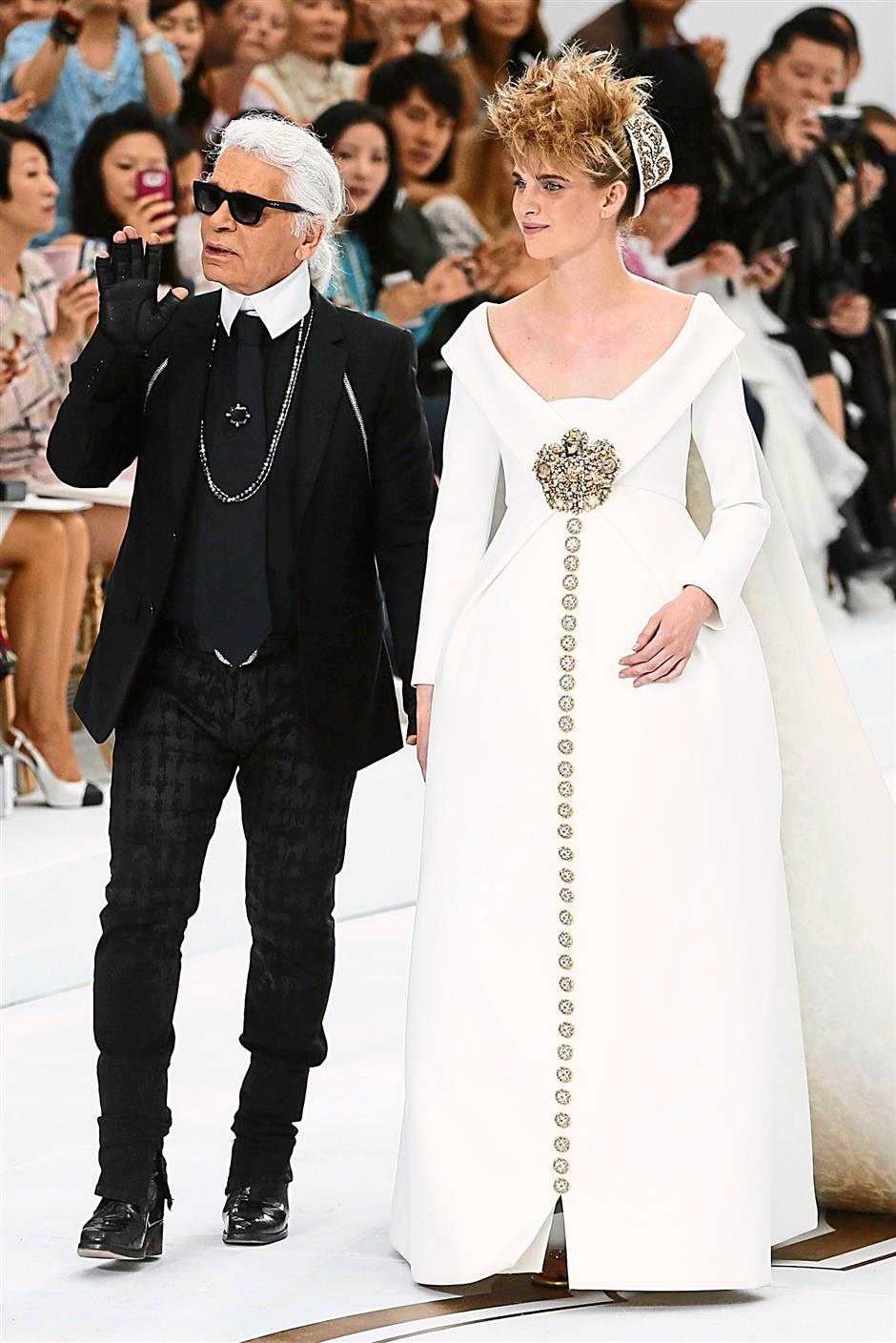 German fashion designer Karl Lagerfeld acknowledges the public with a model at the end of the Chanel 2014/2015 Haute Couture Fall-Winter collection fashion show on July 8, 2014 at the Grand Palais in Paris. AFP PHOTO / PATRICK KOVARIK