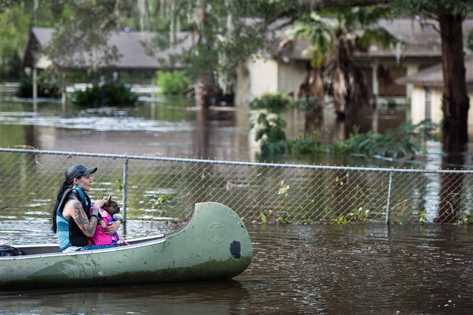 MIDDLEBURG, FL - SEPTEMBER 12: A woman and her dog navigate floodwaters caused by Hurricane Irma on September 12, 2017 in Middleburg, Florida, United States. The storm brought flooding to areas not seen in generations.   Sean Rayford/Getty Images/AFP == FOR NEWSPAPERS, INTERNET, TELCOS & TELEVISION USE ONLY ==