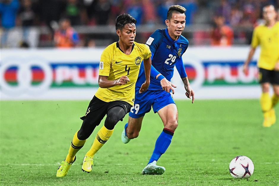 Beat you to it: Malaysia defender Syahmi Safari (left) vying for the ball with Thailand midfielder Sanrawat Dechmitr during the second leg of the AFF Suzuki Cup semi-final match at the Rajamangala Stadium in Bangkok yesterday. — AFP