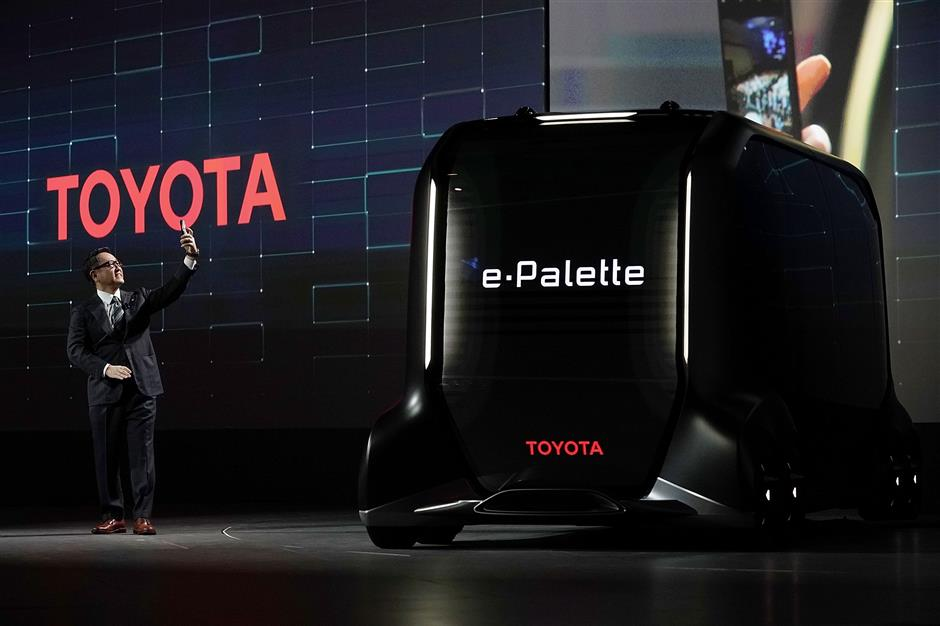 LAS VEGAS, NV - JANUARY 08: President of Toyota Motor Corporation Akio Toyoda takes a selfie after he introduced the e-Palette Concept Vehicle, a fully autonomous, battery-electric vehicle with open control interface to allow partner companies to install their own automated driving system, during a press event for CES 2018 at the Mandalay Bay Convention Center on January 8, 2018 in Las Vegas, Nevada. CES, the world\'s largest annual consumer technology trade show, runs from January 9-12 and features about 3,900 exhibitors showing off their latest products and services to more than 170,000 attendees.   Alex Wong/Getty Images/AFP == FOR NEWSPAPERS, INTERNET, TELCOS & TELEVISION USE ONLY ==